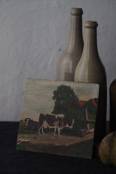 うららか 牛と牛追い犬-oil painting plate 牛の群れとの仕事犬、この油絵の主役は牛ですが、右下から牛を追い立てる犬の存在も大きい。もくもくと繁る樹木の間から覗く朱赤の農家屋根と西側の大空の対比バランスが一層のどか。ノートサイズの小さめな絵は壁にテーマを決め、数枚で一組のディスプレイも有り。今回の場合は、、「田園」さもなくば端的に「牛」で決まり。全体の絵の具にヒビが走っております。木の板に直接油絵の具で描かれており、板の歪みが御座います。背面にフックは御座いません。
