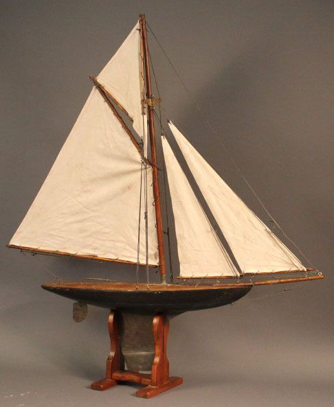 Vintage pond yacht with green and black hull and varnished deck. Rigged with a suit of four ...