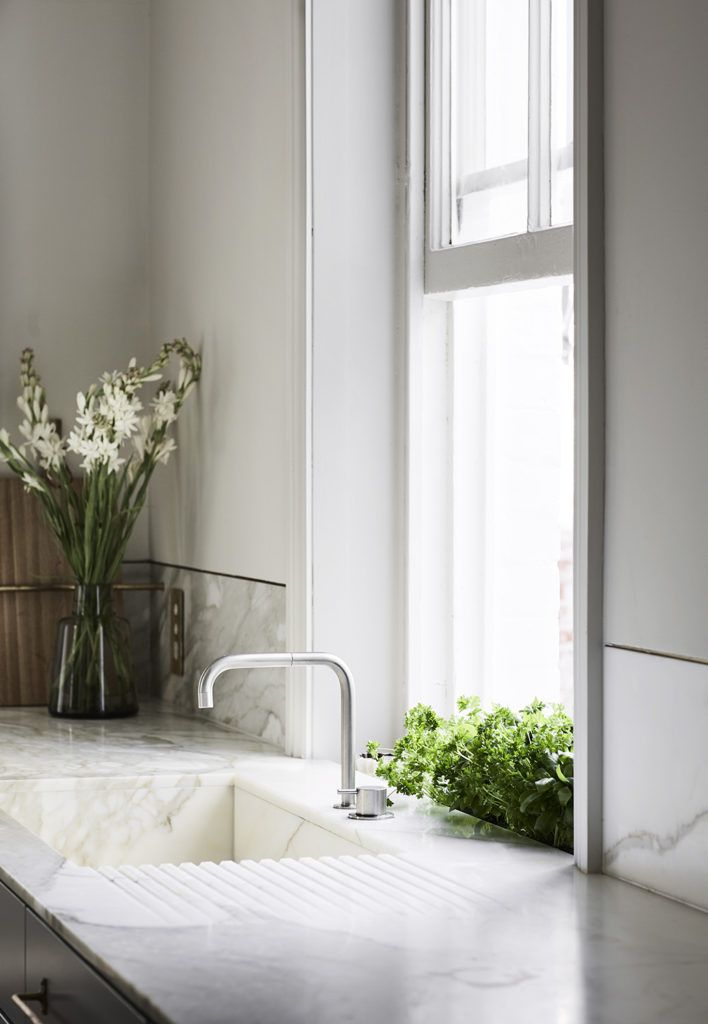 Incredibly luxurious yet understated kitchen with marble sink and sleek chrome tapware. I also love the planter box built into the windowsill!