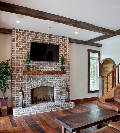 This mortar washed fireplace blends nicely with the white wall and dark wooden beams and floors.