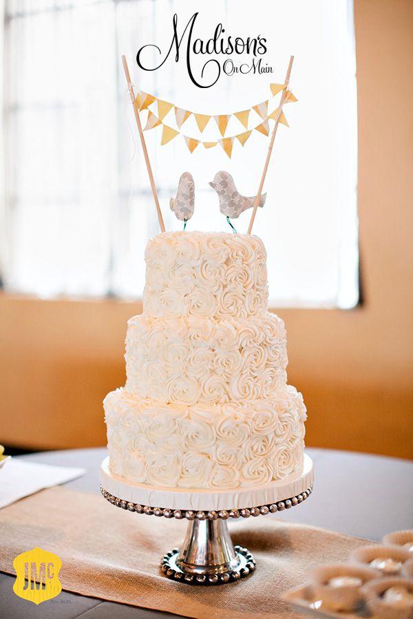 Ivory buttercream rosette wedding cake with bunting bird cake topper.  So sweet!