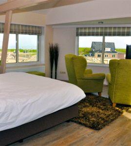 hotelkamer met zitje van groene fauteuils en uitzicht op haven