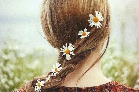 Коса девушки с вплетенными ромашками