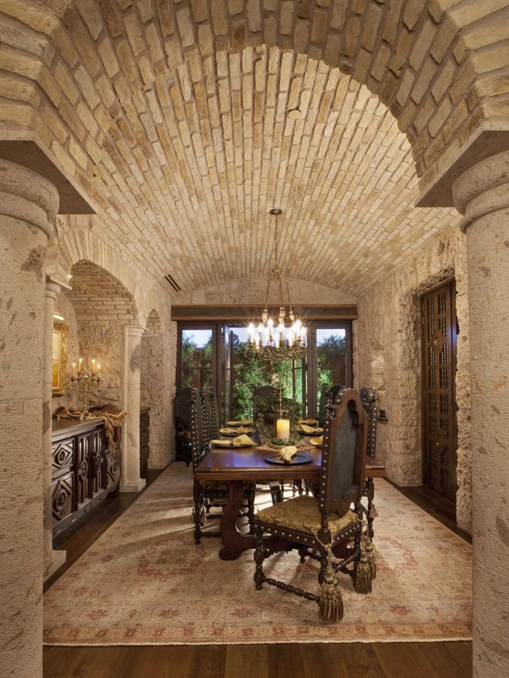 With its brick barrel ceiling and rough stone walls, this dining room could double as a wine cellar. Heavy, hand-carved dining chairs surround a wood dining table under the glow of a filigreed chandelier.