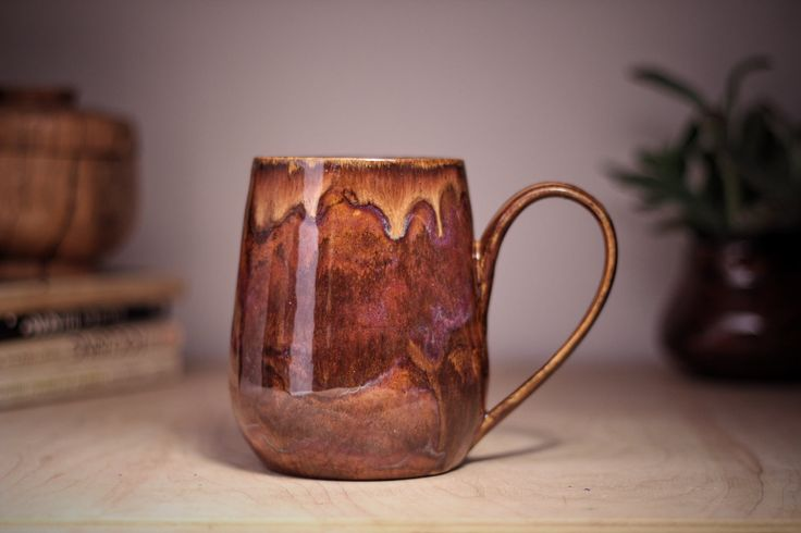 This beautifully organic mug looks like it was hewn from precious stone. It is glazed with rich earthen purple and a dripping, molten golden brown. It has a comfortable four finger handle and its gently sloped base is made to rest comfortably in your palm as you sip your coffee on herbal tea. This eclectic cup would make the perfect gift for the rustic yet classy person in your life. Dimensions: 3 1/8 inches wide at the top, 4 3/4 inches tall and holds 18 oz.  Made on the wheel with...