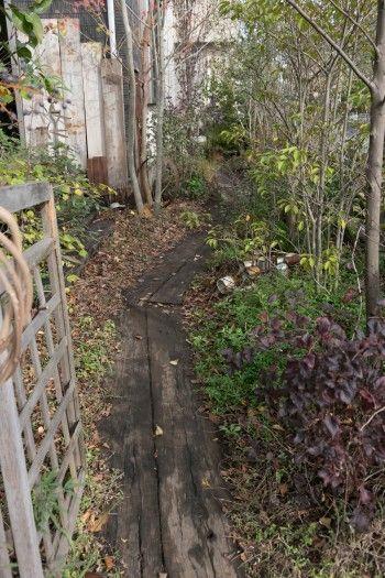 ゆるやかなカーブを描く玄関へのアプローチ。雨の日も歩きやすいように、中古の枕木を敷いた。