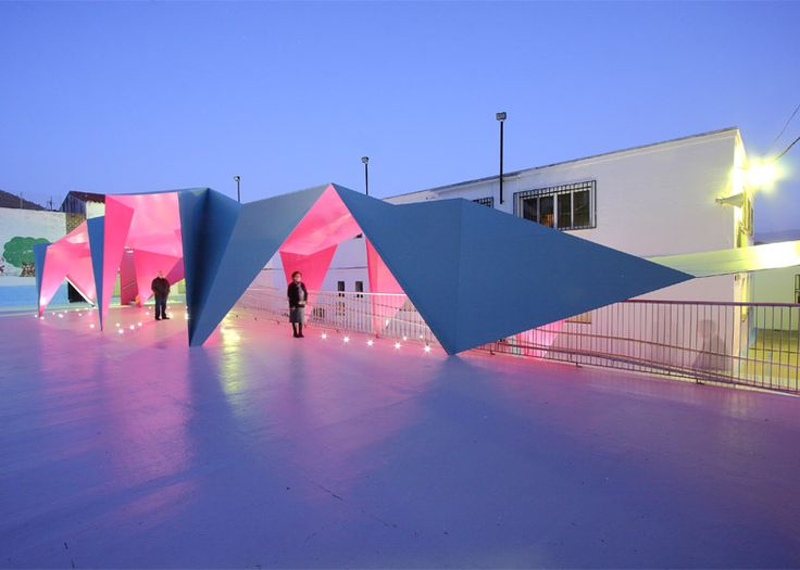 Thin sheets of brightly-painted steel have been folded to create this canopy, which was designed to shelter the playground of a school in Andalusia