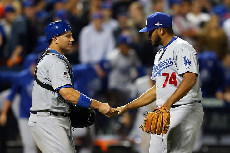 A.J. Ellis #17 and Kenley Jansen #74 of the Los Angeles Dodgers of the Los Angeles Dodgers celebrate after defeating the New York Mets in game four of the National League Division Series at Citi Field on October 13, 2015 in New York City.  The Dodgers defeated the Mets with a score of 3 to 1.  (Photo by Elsa/Getty Images)