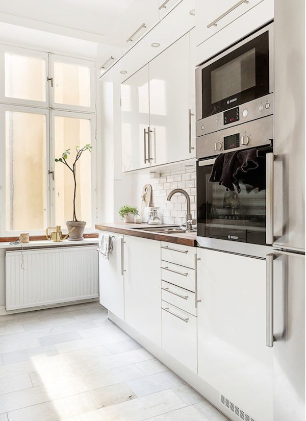 clean, modern kitchen. love the subway tile in this white kitchen.