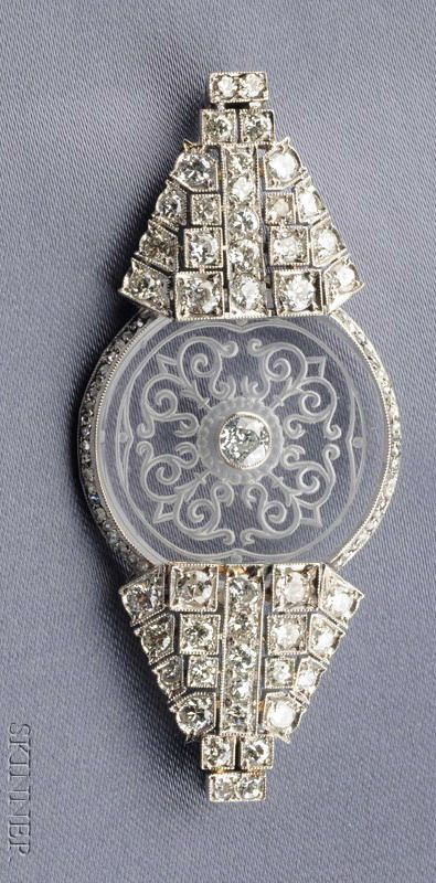 Art Deco ~ Platinum, Diamond, & Rock Crystal Brooch, centering a scroll-etched rock crystal disk flanked by box-set full-cut diamonds, rose-cut diamond accents, approx total wt 2.50 cts, millegrain accents, lg. 2 3/8 in.