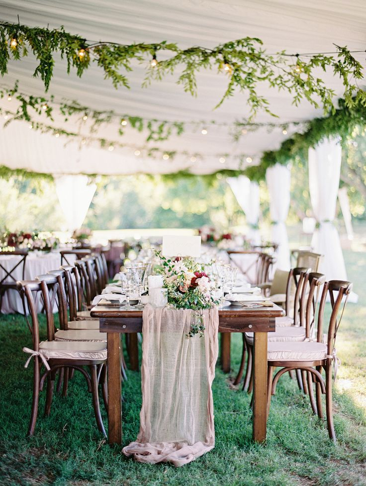 It was straight to the tent for the reception following the ceremony. The drapery and garlands of greenery soften the tent, and the round tables were dressed with mauve velvet cloths. Here, the head table, was dressed with a gauzy runner. Low arrangements of roses, scabiosa, and greenery added more color to the space.    As everyone ate, drank, and mingled, the DJ also shared updates on the Oklahoma Thunder game.