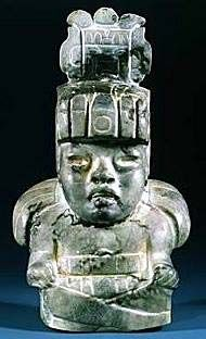 OLMEC God II - Maize Deity. (Author provided) God II was the maize /corn god. It was usually depicted with a maize cob sprouting from a cleft in its head. Sometimes the being was shown as youthful or carved as a toothless infant. It had almond-shaped eyes, thick prominent lips, and a large flat nose. Carvings atop the heads of these statues were common. God II may have been the antecedent of all Mesoamerican corn deities..