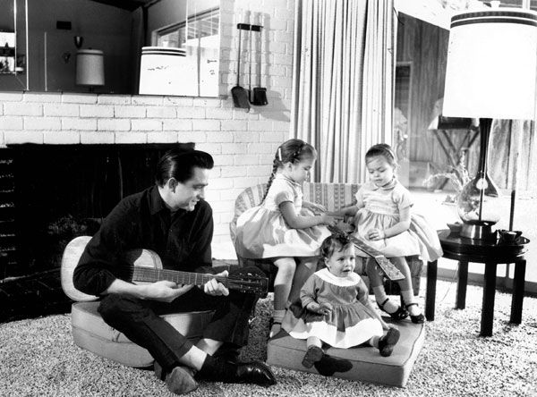 Johnny Cash holding a to guitar, sitting with daughters Rosanne, Cathy and Tara in 1960.