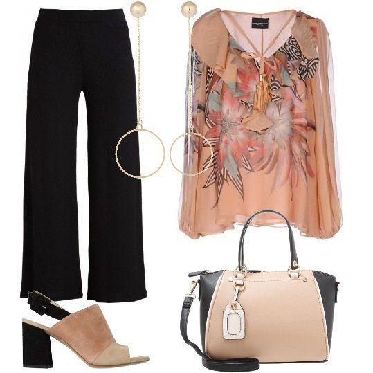 Una blusa di crêpe di seta, con nappine, ruches e fantasia floreale, è indossata con morbidi pantaloni a zampa. Gli accessori sono dei sandali tricolore, in camoscio con tacco geometrico, una borsa bicolore in ecopelle e orecchini pendenti dorati.