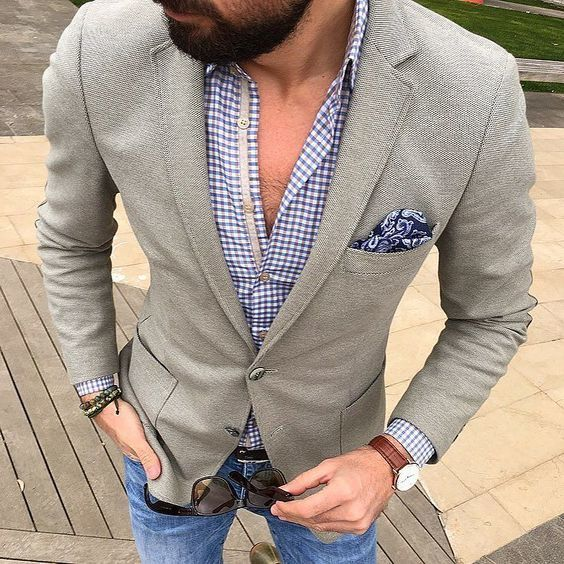 Go for a grey wool blazer and blue jeans if you're going for a neat, stylish look.   Shop this look on Lookastic: https://lookastic.com/men/looks/grey-blazer-blue-long-sleeve-shirt-blue-jeans/21032   — Blue Gingham Long Sleeve Shirt  — Grey Wool Blazer  — Navy Paisley Pocket Square  — Blue Jeans