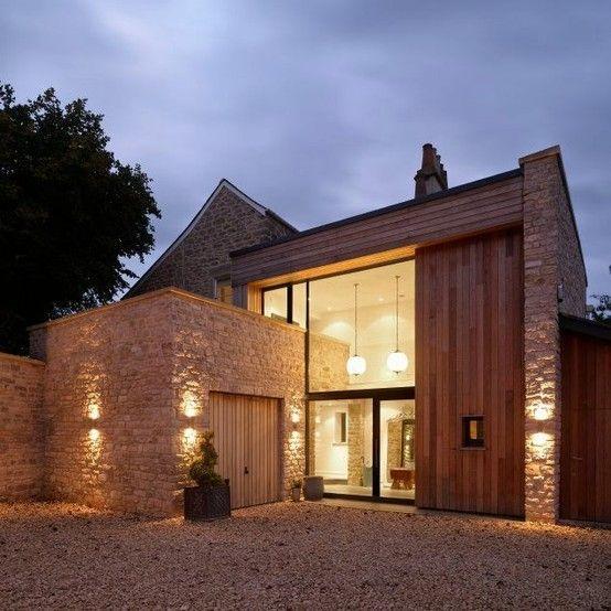 Modern farmhouse. I like how the exterior stone building extends thru the glass into the interior area.