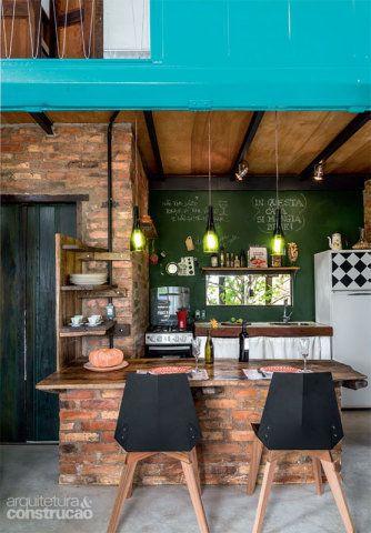 A parede desta cozinha, que fica dentro de uma casa que mescla tijolos aparentes e um contênier, ganhou tinta lousa e se transformou em porta-recados. Projeto de Ferraro Habitat.