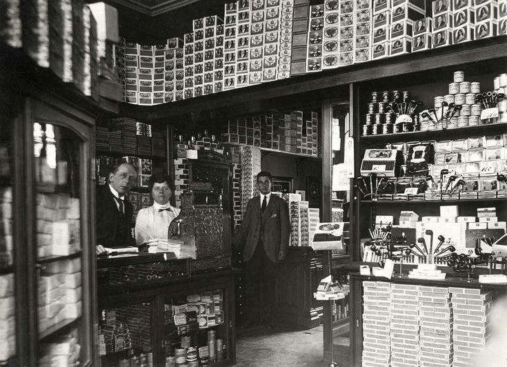 Blik in het magazijn van de sigarenzaak van P.H. Korlvinke en Co aan de Kazernestraat in Den Haag, met personeel achter de toonbank en een groot assortiment rookwaren op stapels in kasten. Nederland, 1921.