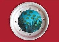 Paper Plate Port-Hole -   You will need:   Light blue construction paper,  Paper or styrofoam plate,   Blue cellophane,   Green tissue paper,   'O' shaped cereals (6-8 pieces),   6-8 Goldfish crackers (multi-colored or reg),   Silver-gray paint.  First draw a circle onto the blue paper using the plate as a guide.   Cut out along the edge of the line, to create your background.   The basic idea is to create a background on the blue paper.