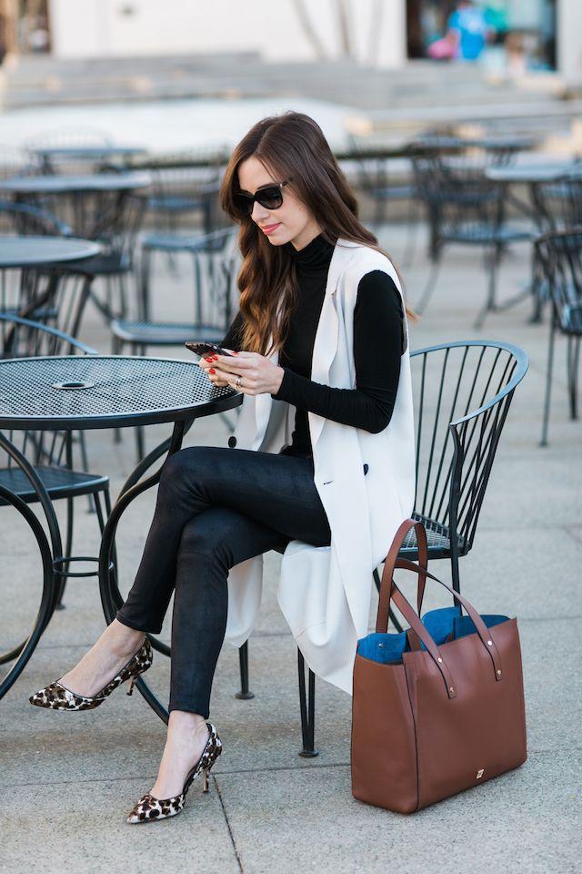 Fall outfit: black turtleneck sweater, cream long vest, black leather pants, leopard pumps, brown bag