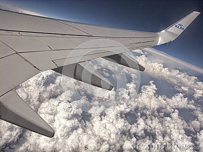 The wing of Boeing 747 of Dutch KLM airlines. Air travel concept with big plane wing over white fluffy clouds.