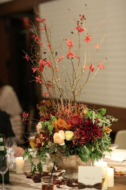 会場は和の雰囲気を取り入れたモダンな和洋折衷な空間。装花は高さのある枝ものを中心に、和風になりすぎないよう淡いピンクのバラを入れて洗練された雰囲気に。「高砂の左右には紅葉樹の柱を作って華やかに、野外の雰囲気を演出してもらいました」。   招待状で使ったリボンに合わせてテーマカラーはブラウンに。ゲストをお出迎えするウエルカムボードは安田さんの双子のお姉さんが描いてくれたそう。「ふたりの家紋&...