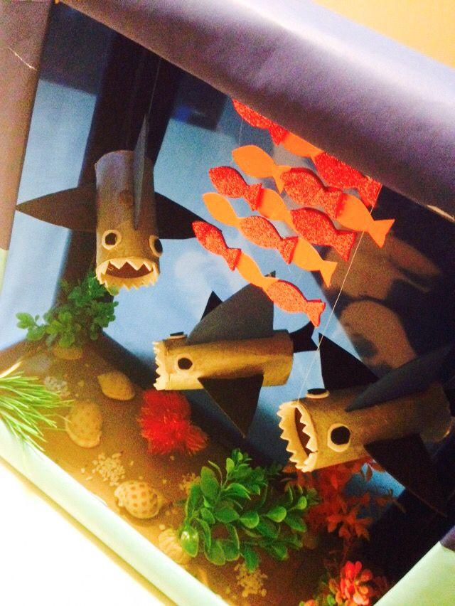 Proyecto Tiburones con caja de cartón y rollos de papel.