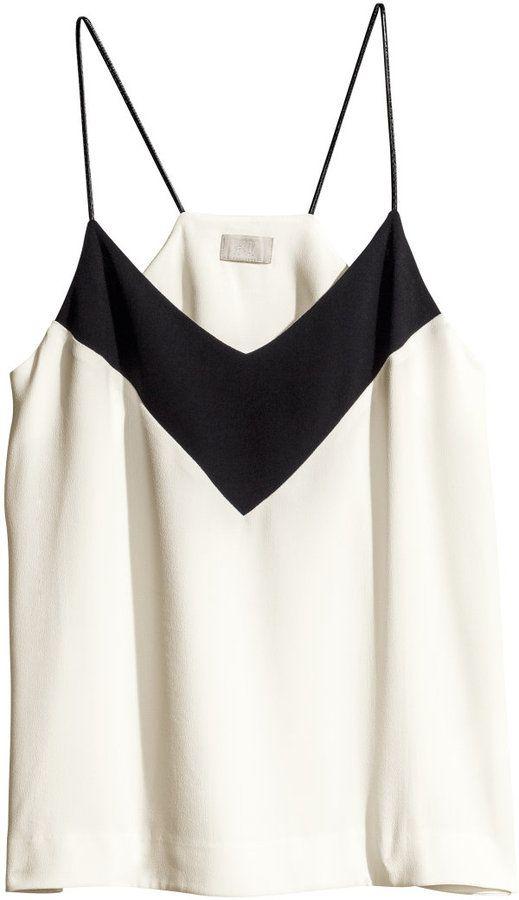 La blusa es blanca y negra. La blusa sin mangas.