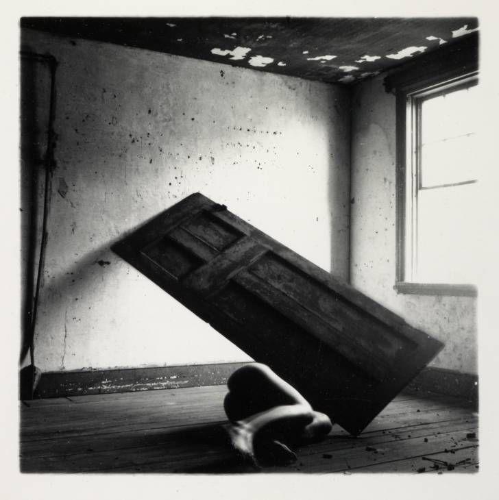 (Metáfora 2) (Francesca Woodman) En esta imagen vemos una puerta a la que parece que se le da un aspecto humano al sumarle la parte inferior de una persona. Al parecer el autor quiere relacionar esta imagen con la soledad o abandono que siente y sufre la gente sola o aislada social mente, al igual que les pasa a las puertas de las casas o pisos abandonados.