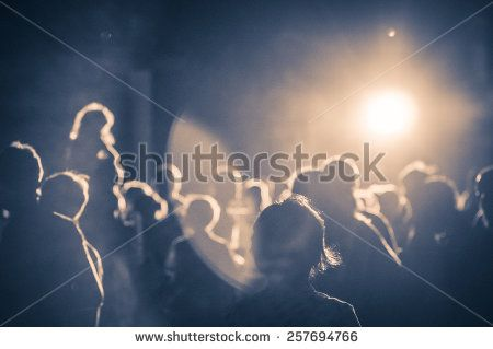 crowd at a concert in a vintage light noise added - stock photo