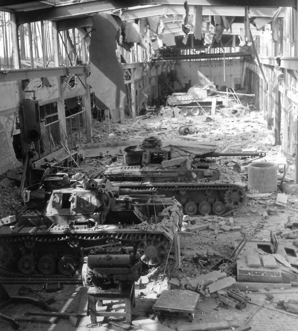 Fantastic picture of 3 panzers in a bomb damaged repair shop.  What's really interesting with this picture is the range of vehicles. In the background there is a Panther in the middle is a late version of the panzer IV with extra armor fitted around the turret.  In the foreground there is a panzer III