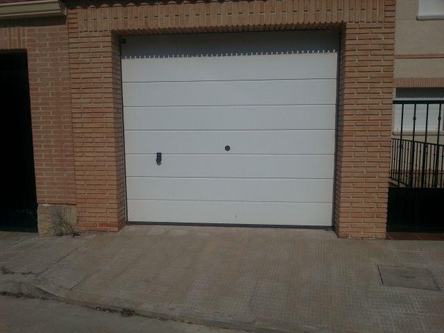 Puertas secciona realizada con panel de con aislamiento l en color blanco. Este tipo de puertas de garaje se apilan en el techo una vez abierta favoreciendo su colocación en espacios reducidos.