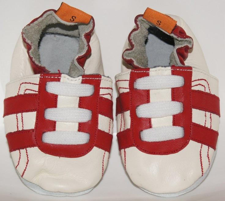 De red trainers zijn sportieve leren babyslofjes met rode strepen.