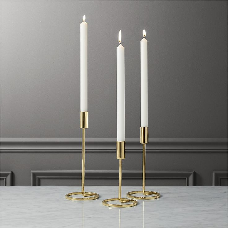 Shop 3-piece roundabout taper candle holder set.   Ring around a golden glow.  Rising to staggering heights, three brass-plated steel sculptures ascend a single taper holder from a circular base.  We like them lined up or in a round.