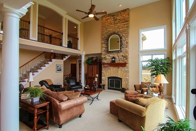 Gorgeous great rooms love the two story stone fireplace for Balcony living room design