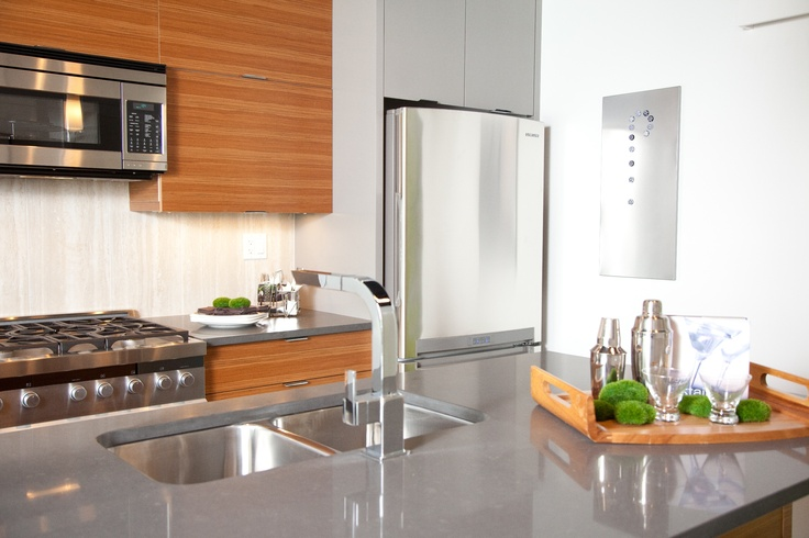 Quartz countertops and echo wood cabinets with gas range, stainless steel appliances, undermount sink and kitchen bulletin board in modern apartment kitchen at The Block by Avi Urban