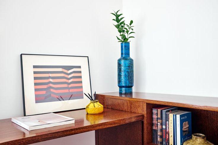 Detalhe escritório - Bancada e prateleiras de marcenaria com folha natural de Sucupira e gabinete com fórmica azul. Piso de taco de madeira restaurado e luminária Reka.