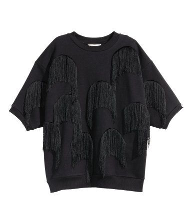 Black. Soft, wide-cut sweatshirt top with decorative fringe and short sleeves. Ribbing at neckline, cuffs, and hem.