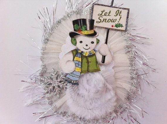 Ornamento de topetón del chenille estilo vintage... Muñeco de nieve vestido con sombrero, chaleco y pañuelo adornado con glitter con cuerpo de chenille blanco mullido... llevar una pancarta de Let it Snow! con bordes en brillo y con un brillo de plata copo de nieve... en un brillo blanco tarjeta stock festoneado oval... filo con volantes papel crepe blanco cortado en glitter Plata... adornado con Plata oropel... aproximadamente 4 no incluye la suspensión de la cuerda de plata...  Estas…