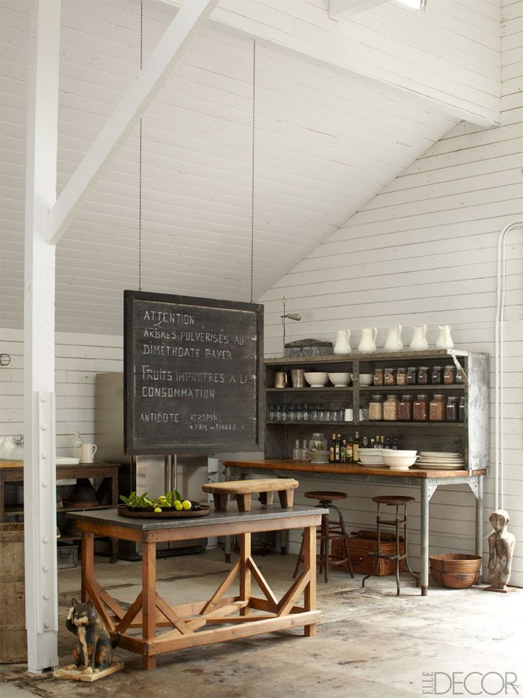 Read more: Ellen DeGeneres Portia de Rossi Santa Monica Home Kitchen - Southern California Horse Ranch - Elle Decor May 2013 :: A 19th-century Swedish chalkboard hangs above a 1900 French bluestone-top table in the Art Barn; the antique baker's rack is from Brenda Antin, and the walls are painted in Farrow & Ball's All White. | #farmhouse #farmhousedecor