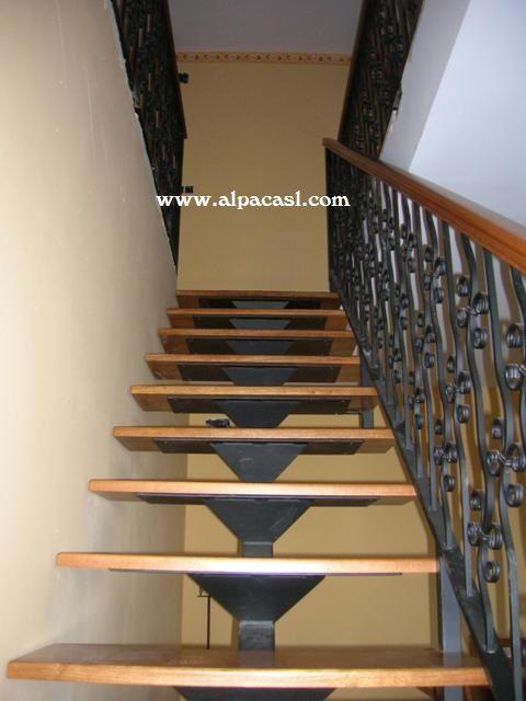 escalera de estructura metlica con eje central y pasos en madera con barandilla de forja