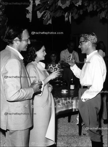 Le 16 juillet 1966, à Saint-Jean Cap-Ferrat (France), le jeune couple d'acteurs, Romy SCHNEIDER (au milieu) et Harry MEYEN (à droite) discutent après la cérémonie de leur mariage, avec un de leurs invités. Les deux acteurs tournent alors ensemble dans TRIPLE CROSS de Terence YOUNG.1966-07-16
