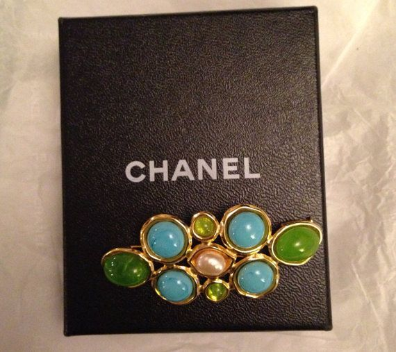 1993 Chanel brooch. Pearl centre surrounded by turquoise and lime green cabochon stones in a French style. Cartouche on clasp marked made in France 93 P.  P meaning spring collection. In mint condition. Includes Chanel box. 3 inches (7 3/4 cm) Width  1 inch (1 3/4 cm) Height Includes Chanel box    Postage prices are guidelines only, these can change.  Shipping excludes South America, Central America, China, Africa, India, Vietnam and Thailand.