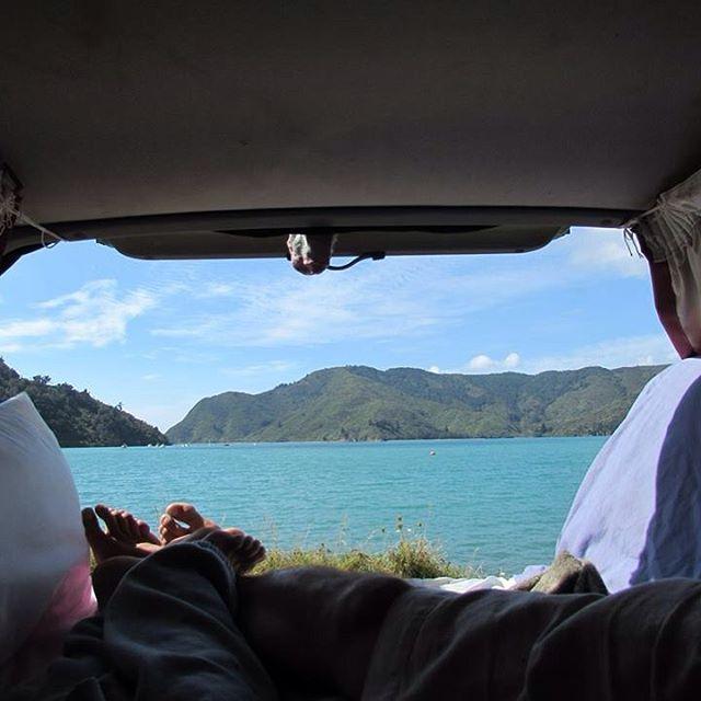 ⛽️TRAVELLING BY VAN: my dream road trip came true! @robbieallenart. Cair na estrada por 52 dias explorando um lugar paradisíaco como a Nova Zelândia com muito pouco: uma van e um amor internacional.. Adoro essa nossa foto descansando de frente para o rio depois do piquenique no almoço - apesar da meia secando no nosso varal improvisado!  #nomadiccarol #carolprates #newzealand @purenewzealand