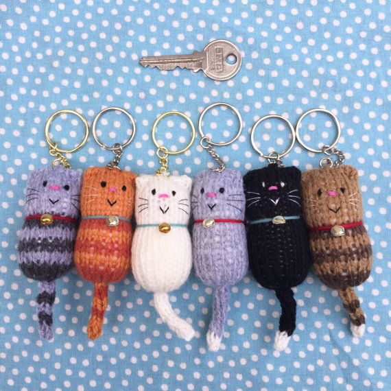Made to order keyring, featuring our Original Design hand knitted cat in a variety of colours, complete with wool collar and tiny tinkling bell. Embroidered features make each little character unique.  Bespoke custom order requests invited: message a photo of your cat, including its back and tail. When ordering, click on the Custom Order colour variation. These keyrings fit our Hand Printed Cat Gift Boxes perfectly, making them lovely gifts for any cat lover. Gold or silver coloured bell and…