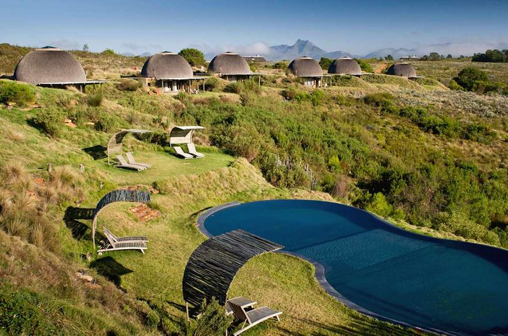 Kwena Lodge swimming pool. Shaded deck chairs surround the pool. Mountain views from Gondwana Private Game Reserve.