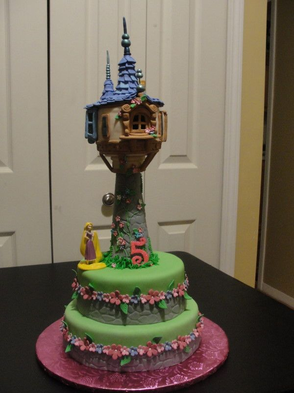 Disney's Tangled Tower Cake - I made this for my nieces 5th B-day. The tower is rice crispy treats, and upper part of ice cream cone where the tower and housing meet. Used fondant and gum paste on tower all windows and decor held together with royal icing, Cake was strawberry with strawberry icing covered in fondant.
