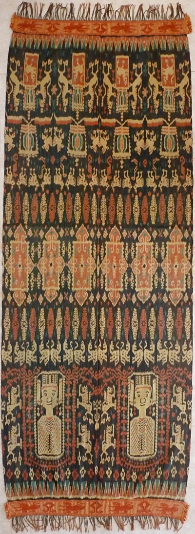 Hinggi, Ikat, 1930-1940, Sumba, Indonesia One half displays portraits of crowned Queen Wilhelmina (busts) and climbing lions, other displays Dutch coat of arms. Pagi-sore, top and bottom entirely different. Wide kabakils (woven borders) with lions. Kayu kuning tinge.
