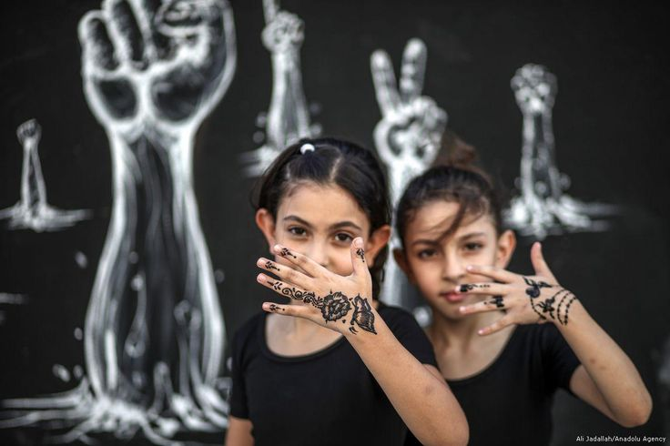 Palestinian girls have their hands decorated with henna...