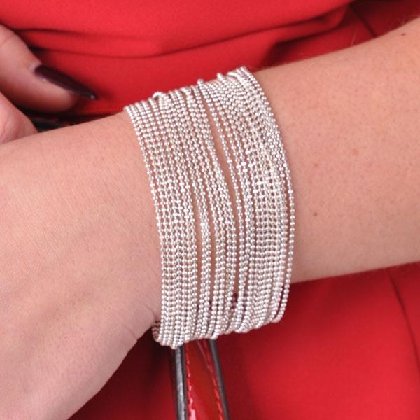 Zilveren armband als opvallend accessoire op een witte jurk